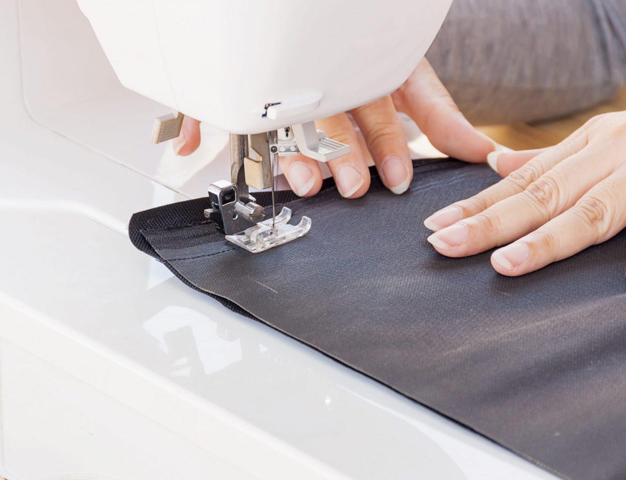 mãos de uma mulher costurando com uma máquina de costura