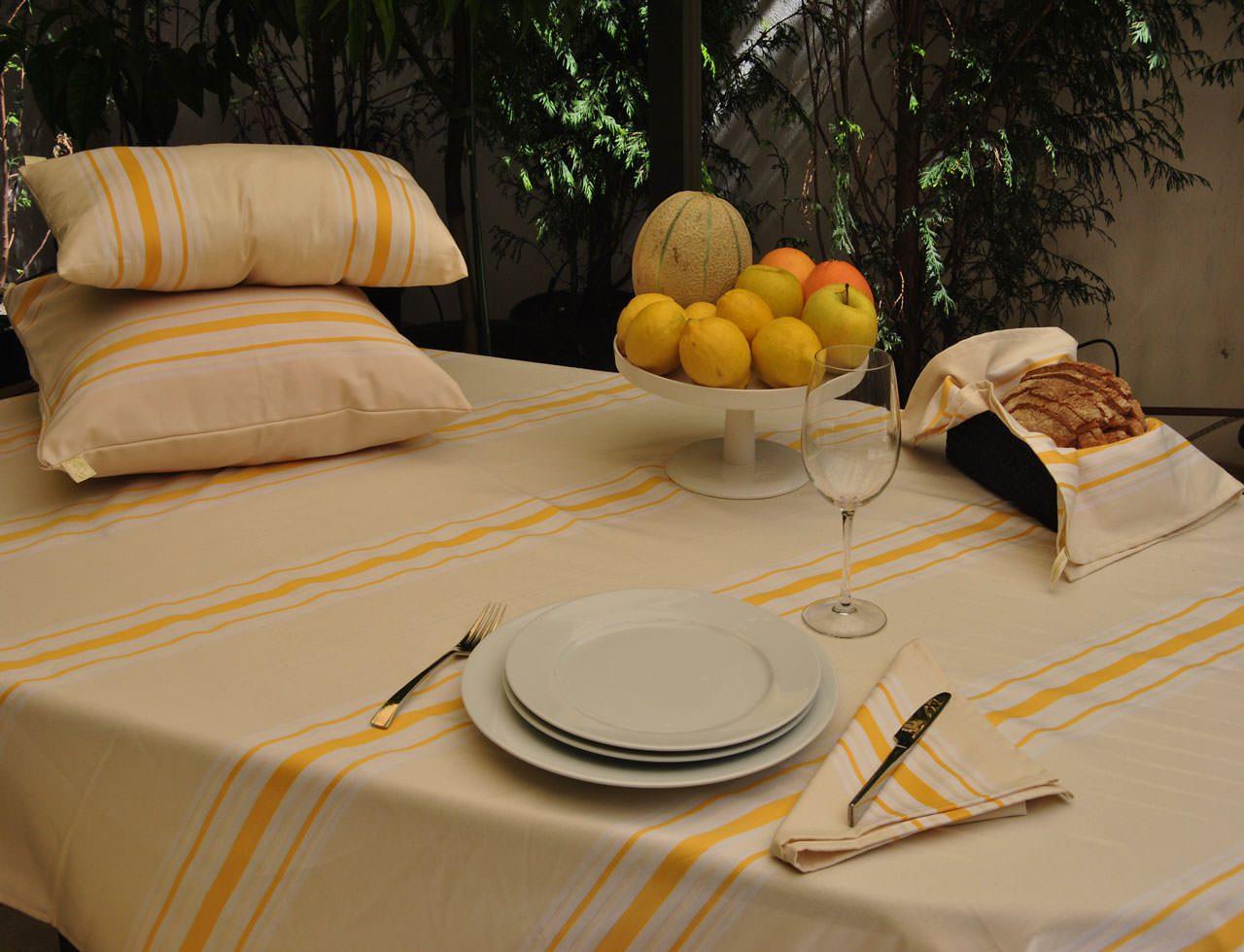 mesa com uma toalha de mesa, almofadas, fruta e pratos